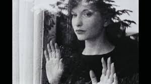 "Frame from Maya Deren's 1943 film ""Meshes of the Afternoon."" Deren is standing at the window, looking out, her hands pressed against the glass."